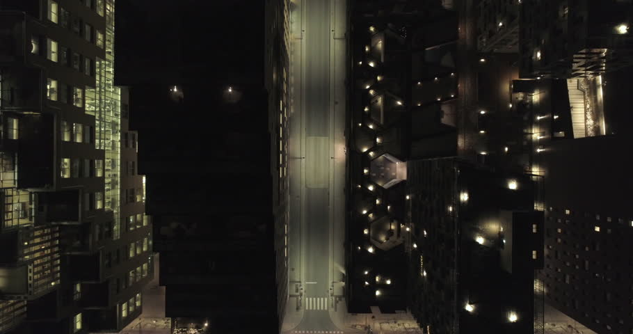 4K aerial video with forward motion and a birds eye view of the dark rooftops of financial- and apartment buildings and an illuminated empty street at night in downtown Oslo, Norway.
