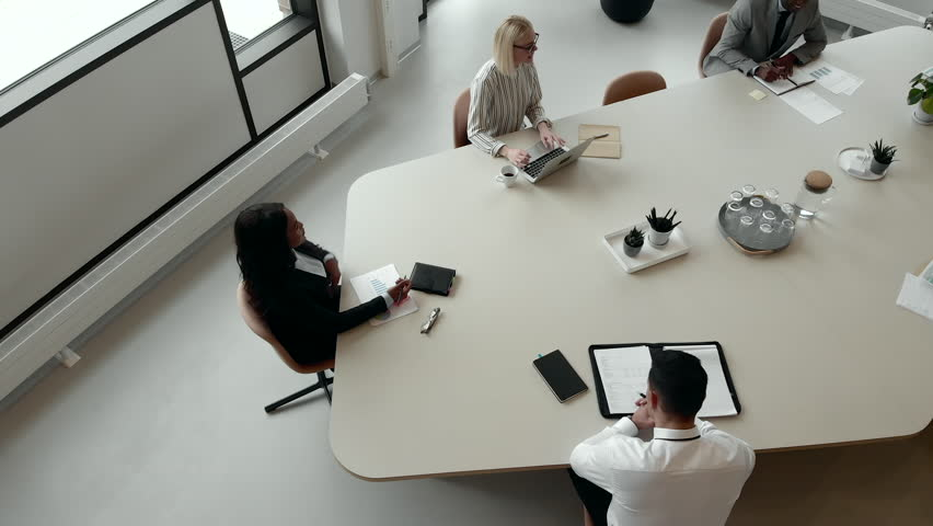 High angle of a diverse group of businesspeople talking together during a meeting around a table in an office boardroom Royalty-Free Stock Footage #1028171285