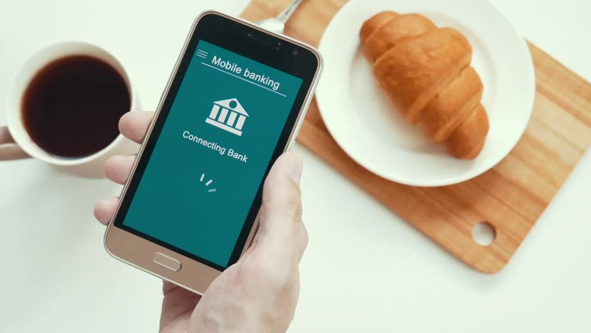 Some trouble with mobile banking in the smartphone. Online bank cannot connect. Smartphone in the hand. Breakfast. Blue custom interface design. | Shutterstock HD Video #1028174939