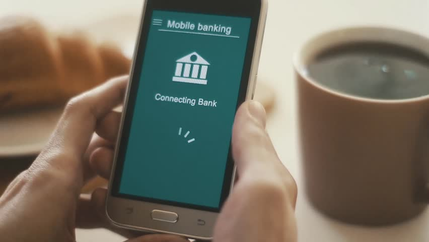 Some trouble with mobile banking in the smartphone. Online bank cannot connect. Smartphone in the hand. Breakfast. Blue custom interface design. | Shutterstock HD Video #1028174942