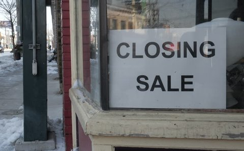 Close up of a closing sale sign in the window of an old store which is going out of business.