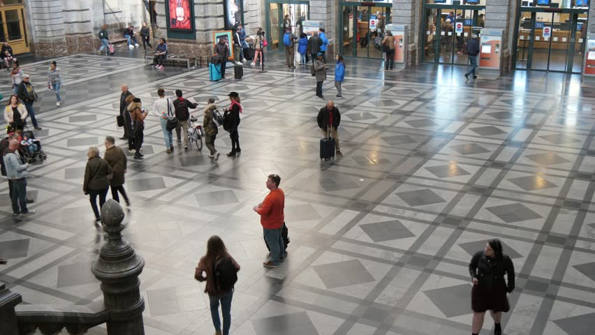Antwerp, Belgium - April 1, 2019:Up down view of Antwerp train station with many people walking in a spacious hall with smooth marble floor with squares in slo-mo