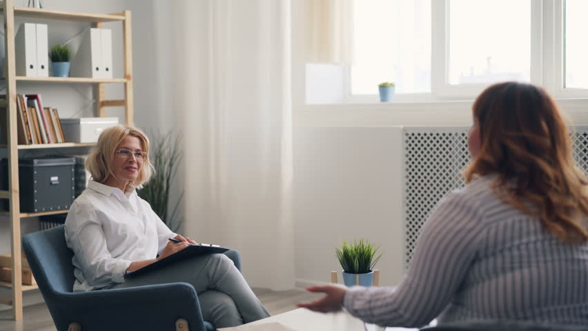 Successful psychologist mature lady is talking to overweight young woman during therapy session in modern clinic. People, conversation and mental health concept. | Shutterstock HD Video #1028213921