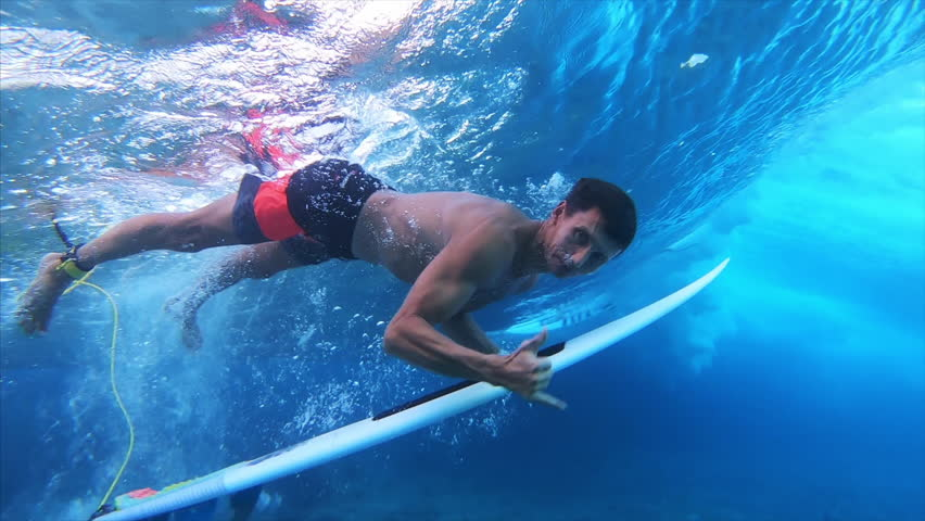 Surfer dives under the wave with the surfboard (the trick named in surfing as Duck Dive) looks into the camera and shows the Shaka sign | Shutterstock HD Video #1028220902