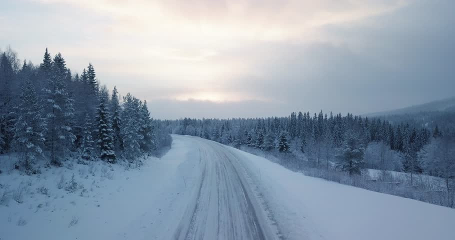 Aerial of car driving in winter paradise in Norway. Surrounded by snow and trees. Royalty-Free Stock Footage #1028222978