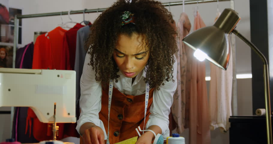 Front view of African American woman fashion designer looking at cloth samples in workshop. She is examining clothe samples