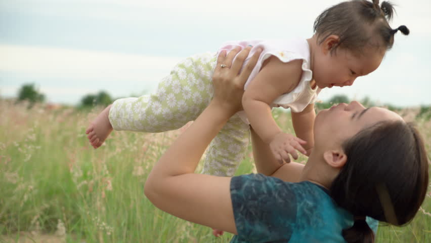 Asian young mother and daughter in the grass field at sunset. #1028246882