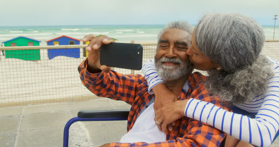 Front view of active senior African American couple taking selfie with mobile phone on promenade. Senior woman embracing and kissing him on cheek.