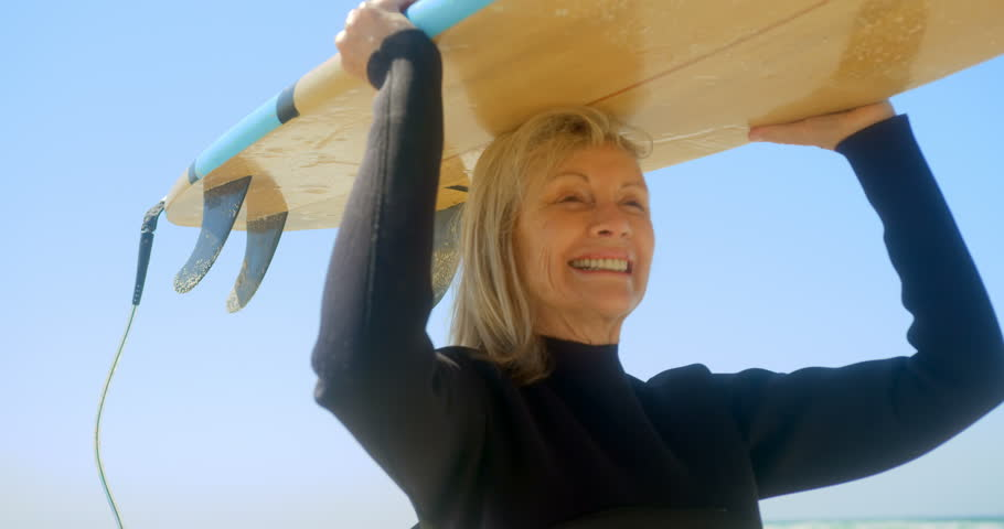 Front view of active senior Caucasian female surfer carrying surfboard on her head at beach. She is smiling and looking away.