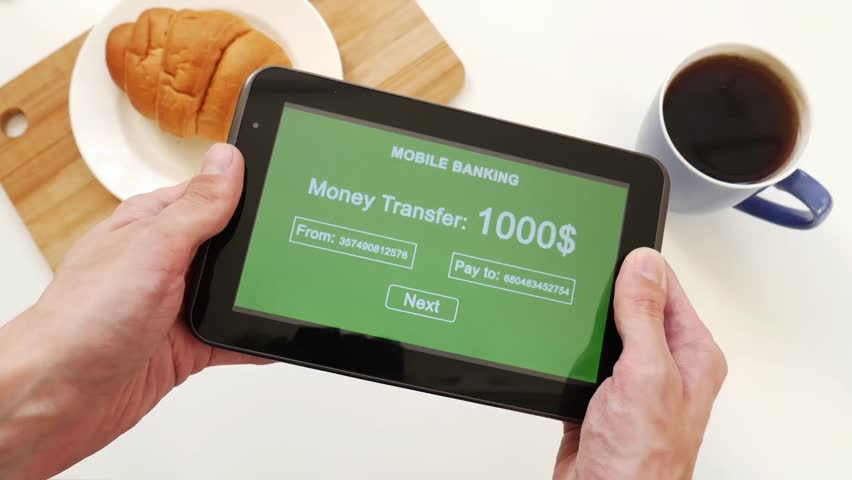 A successful person makes a money transfer through a mobile bank, having breakfast with a croissant and coffee. Green custom interface design | Shutterstock HD Video #1028255546