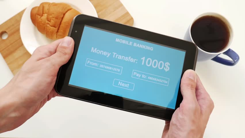 A successful person makes a money transfer through a mobile bank, having breakfast with a croissant and coffee. Blue custom interface design   Shutterstock HD Video #1028255549