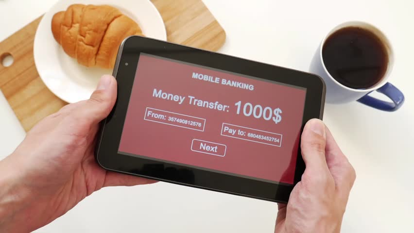 A successful person makes a money transfer through a mobile bank, having breakfast with a croissant and coffee. Green custom interface design | Shutterstock HD Video #1028255552
