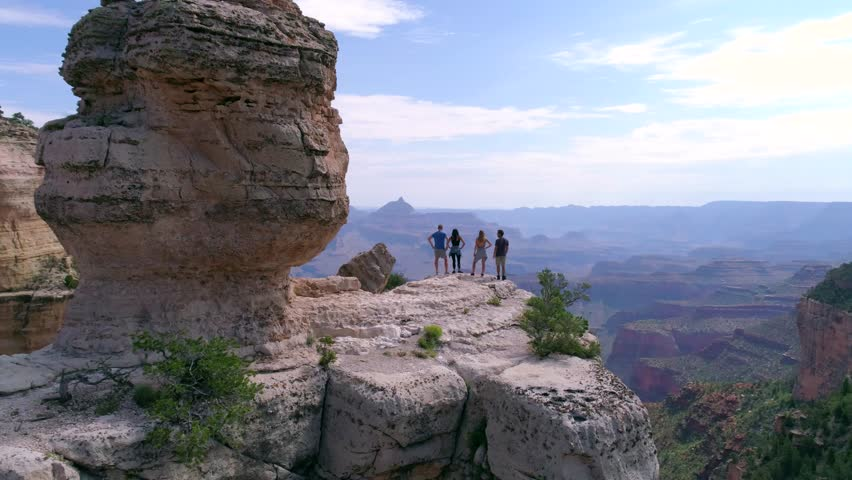 Hikers Looking Into the Grand Canyon by Aerial Drone