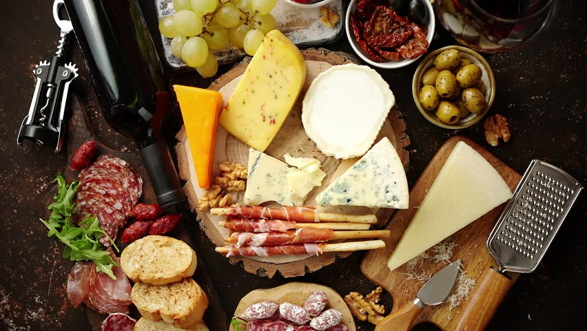 Huge assortment of various tasety spanish, french or italian apertizers. Cheese, meat, olives, stuffed peppers, bread, sticks. Placed on rusty dark background. View from above.
