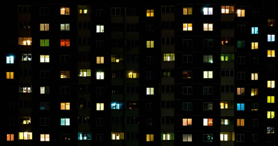 Night time lapse of Light in the windows of a multistory building. life in a big city. Serenade of light