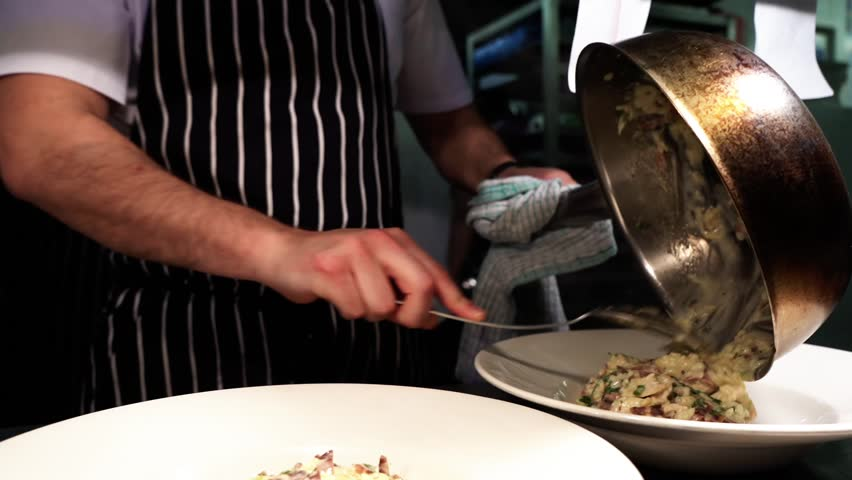 Chef dishing up steamy food onto a plate | Shutterstock HD Video #1028270474