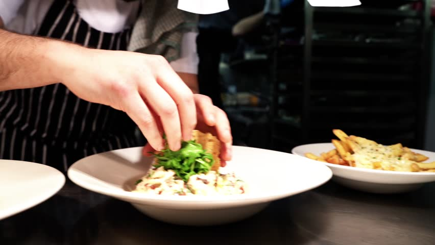 Chef putting the finishing touches onto a plate | Shutterstock HD Video #1028270477