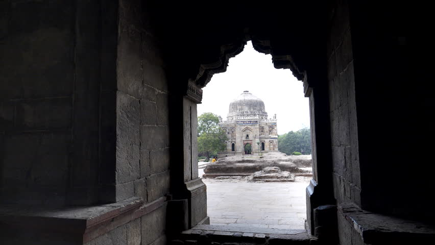 Gimbal clip walking towards shish gumbad framed by an arch of bada gumbad at lodhi gardens in delhi, india   Shutterstock HD Video #1028271278