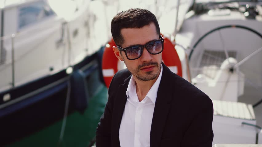 Young handsome man on a yacht. Serious businessman in sunglasses in a suit. Stylish modern guy on deck topside with lifebuoy. Luxury VIP model sitting | Shutterstock HD Video #1028274629