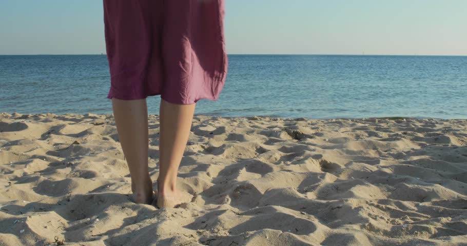 A young woman strips down to her bikini and walks into the ocean on a sunny day   Shutterstock HD Video #1028281658