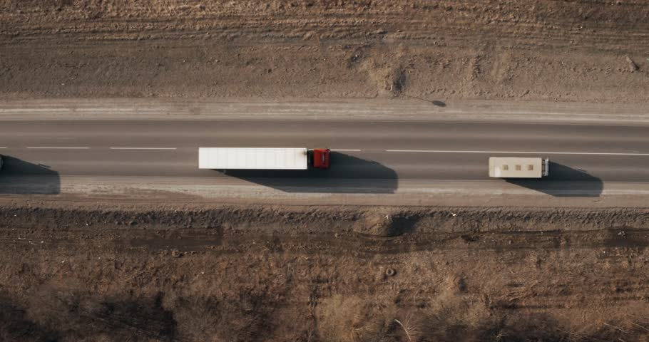 Two Trucks driving / traveling on highway aerial footage at spring time / top down view / Highway truck traffic