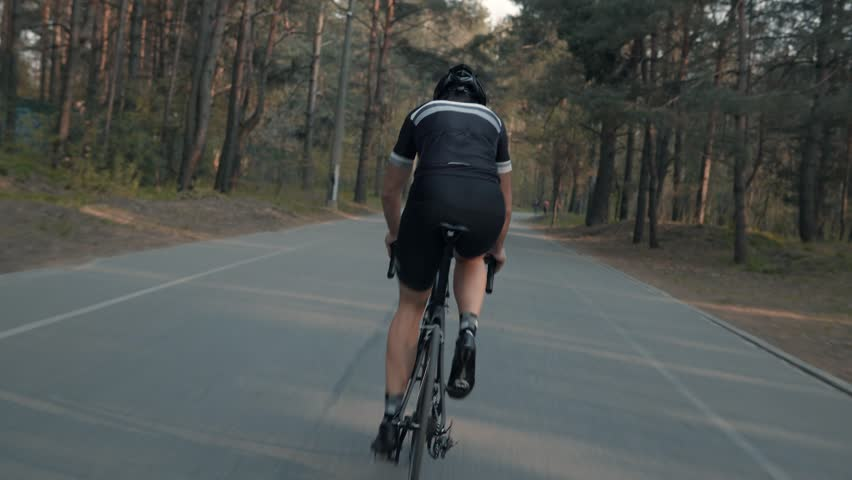Cyclist Riding On Road Bike Rear View.Cycling Men Pedaling Road Bicycle On Park.Triathlete Exercise On Road Bike At Sunset.Cyclist Professional Athlete Workout Training For Triathlon.Sport Concept. | Shutterstock HD Video #1028288954
