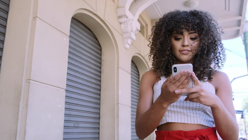 Young curly hair black woman walking using cell phone. Texting on street. Big city. 4k Cinematic. Royalty-Free Stock Footage #1028307005