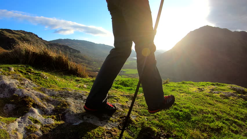 Wales UK - November 2018: Boots and Nordic walking poles of female hiker on her trekking adventure expedition #1028325314