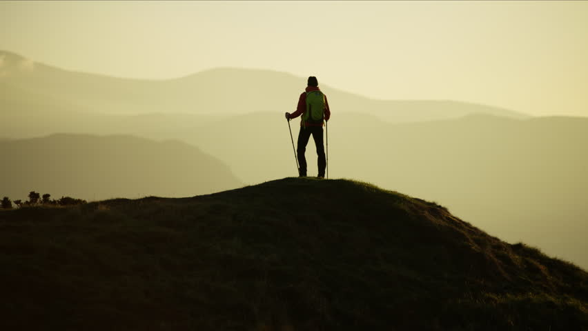 Silhouette of Caucasian European female adventure hiker on her vacation hiking mountain at sunset Snowdonia National Park Wales RED MONSTRO #1028325593