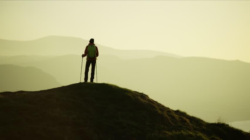 Silhouette of fitness Caucasian European female hiker with Nordic sticks and rucksack enjoying trekking Snowdonia National Park Wales RED MONSTRO | Shutterstock HD Video #1028325695