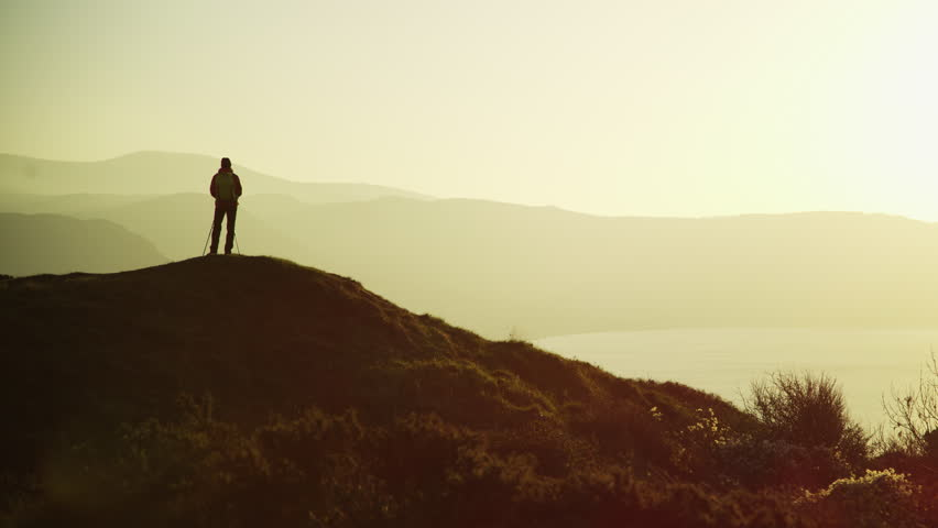 Silhouette of fitness Caucasian European female hiker with Nordic sticks and rucksack enjoying backpacking Snowdonia National Park Wales RED MONSTRO #1028325755