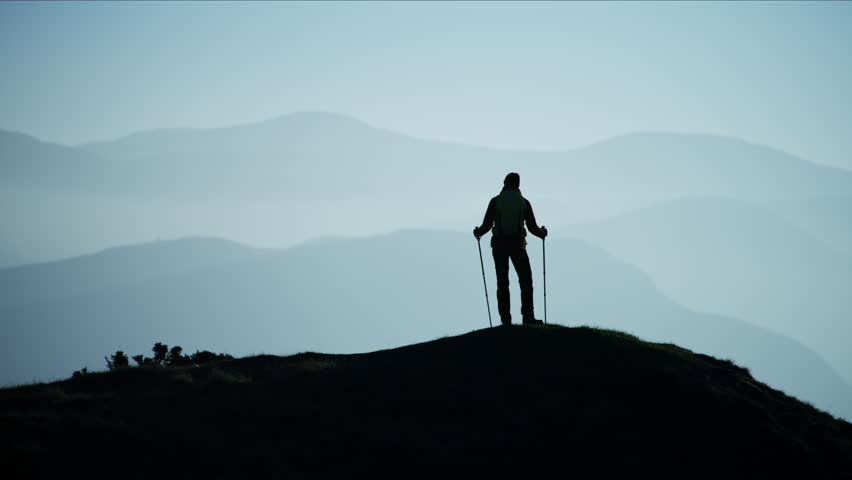 Silhouette of fit Caucasian European woman hiker Nordic walking mountains outdoors at sunset Snowdonia National Park Wales RED MONSTRO #1028325947