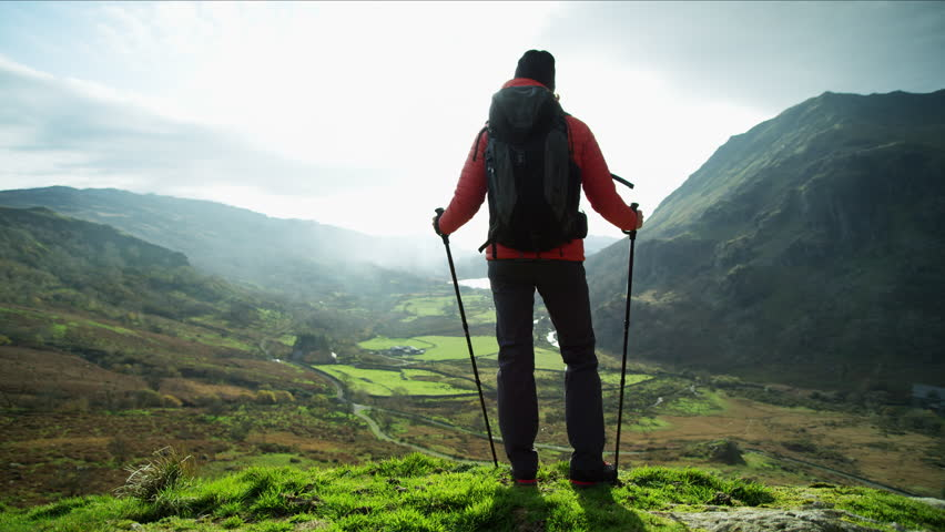 Fit Caucasian European female adventure hiker enjoying Nordic walking on the top of mountain sun flare Snowdonia National Park Wales RED MONSTRO | Shutterstock HD Video #1028326190