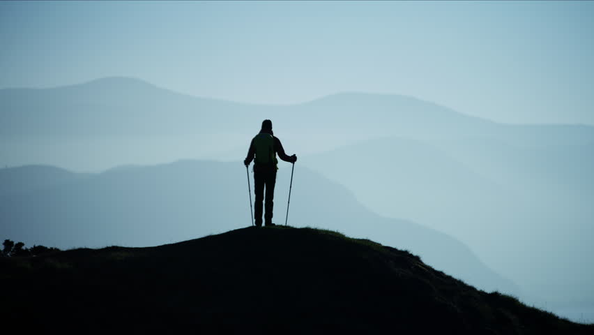 Silhouette of active Caucasian European female hiker achieving her ambitions on the top of mountain Snowdonia National Park Wales RED MONSTRO #1028326382
