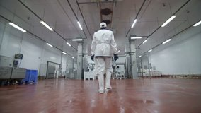 Follow footage of factory worker in cap that is walking through industrial facilities in meat plant. Sausage production