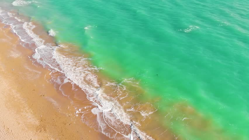 Top view of a superb lonely and deserted beach on the shores of the azure sea. Dawn of nature in 4K. A bird's eye view of ocean waves crashing against an empty beach from above #1028336846