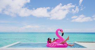 Vacation woman on inflatable Flamingo float mattress using mobile cell phone in swimming pool. Girl relaxing sunbathing enjoying travel holidays at resort pool in bikini. Luxury lifestyle.