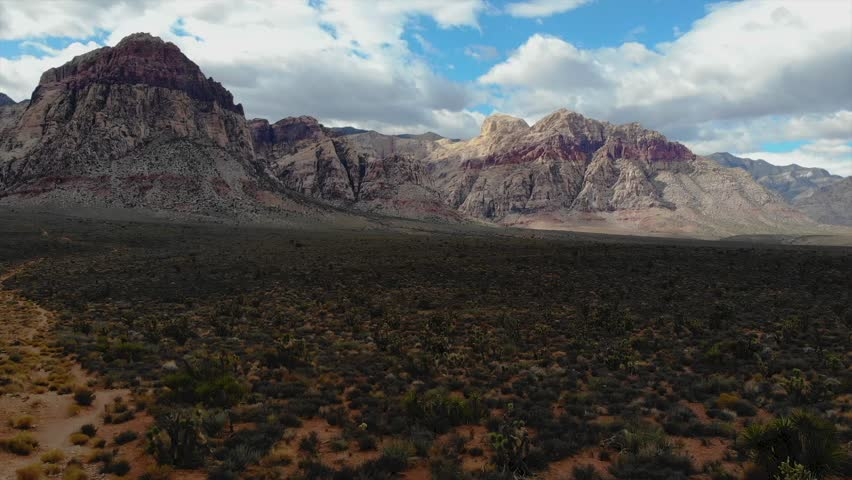 4K resolution, aerial drone at 24 frames per second over mountain in Red Rock Canyon National Park and Desert outside Las Vegas, Nevada with cloudy skies (speed ramping / fast forward / sped up)