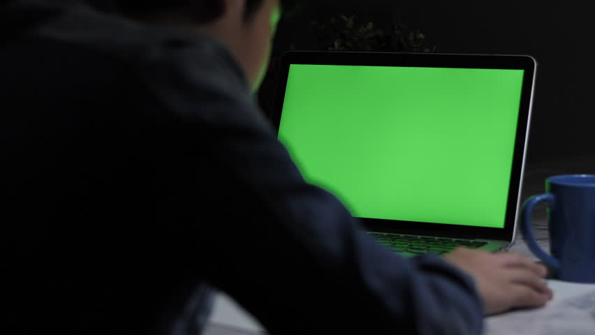 Over the shoulder shot of a young boy using on laptop computer on desk, looking at green screen. Dolly shot 60fps.