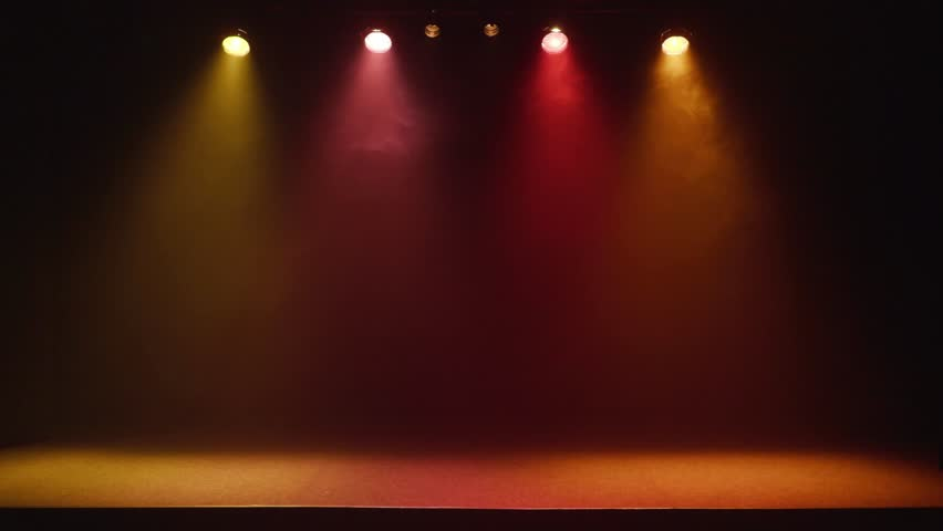 The stage of a small theater with colorful spotlights flashing on and off. Lights are turned on from darkness.