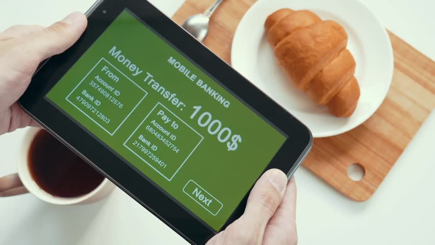 A successful person makes a money transfer through a mobile bank, having breakfast with a croissant and coffee. Green custom interface design. The interface is not real. Information fictional. | Shutterstock HD Video #1028362763