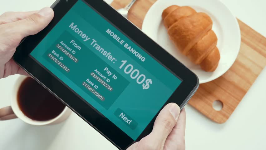 A successful person makes a money transfer through a mobile bank, having breakfast with a croissant and coffee. Blue custom interface design. The interface is not real. Information fictional. | Shutterstock HD Video #1028362766