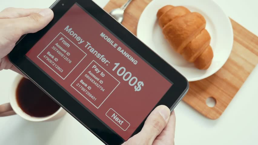 A successful person makes a money transfer through a mobile bank, having breakfast with a croissant and coffee. Red custom interface design. The interface is not real. Information fictional. | Shutterstock HD Video #1028362772