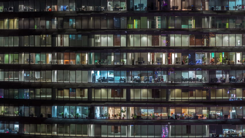 Working evening in glass business centre office building with numerous offices with glass walls and illuminated windows timelapse. People sitting at desks #1028367179