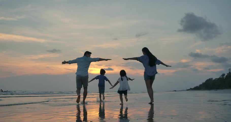 Silhouetted happy asian family playing and having fun on the beach at sunset. Slow Motion. Family, Freedom and Travel concept. Royalty-Free Stock Footage #1028374757