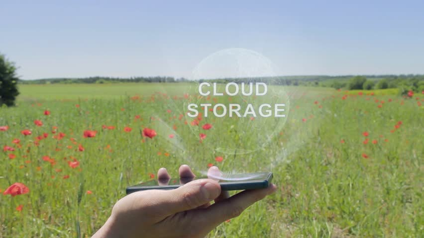 Hologram of Cloud storage on a smartphone. Person activates holographic image on the phone screen on the field with blooming poppies | Shutterstock HD Video #1028381072