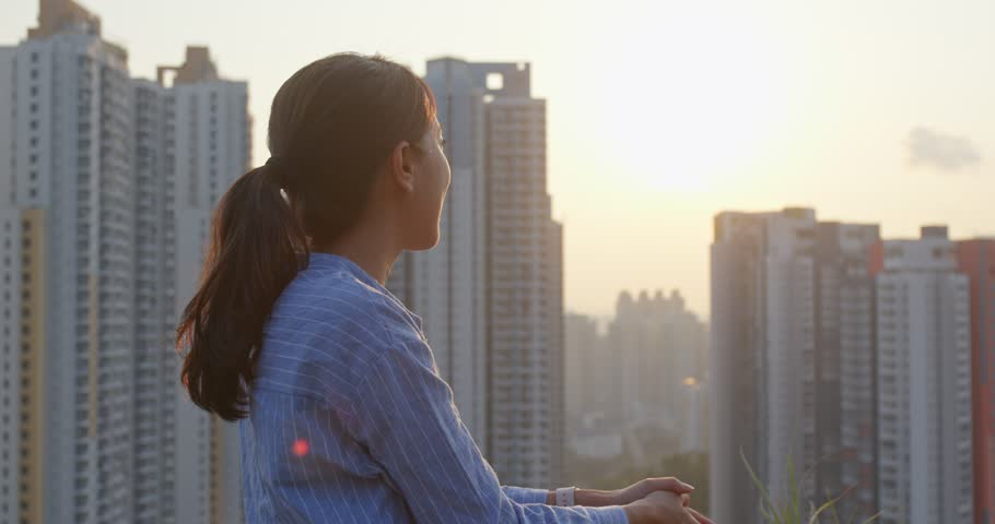 Woman enjoy the view of sunset in city of Hong Kong