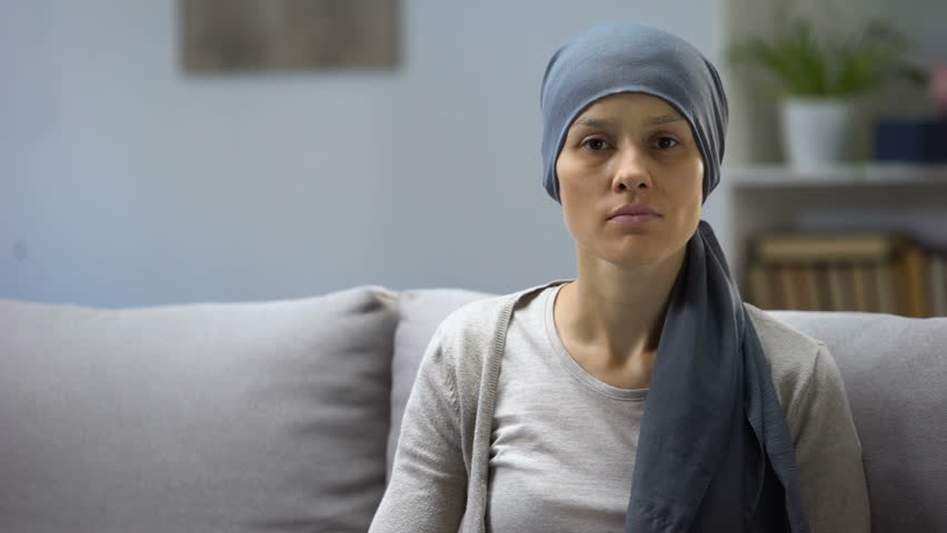Woman after chemotherapy sitting at home and looking into camera, background | Shutterstock HD Video #1028393834