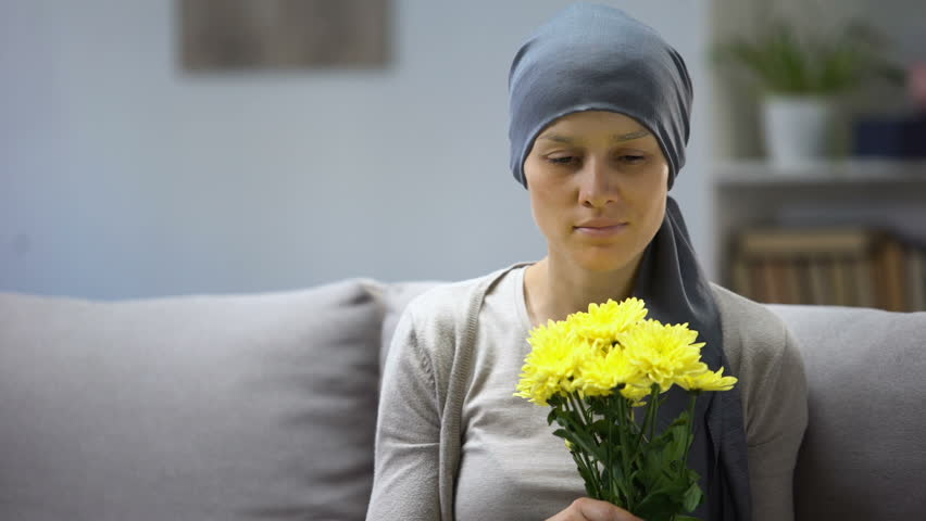 Recovery after cancer, woman in headscarf smelling flowers and enjoying life | Shutterstock HD Video #1028393855
