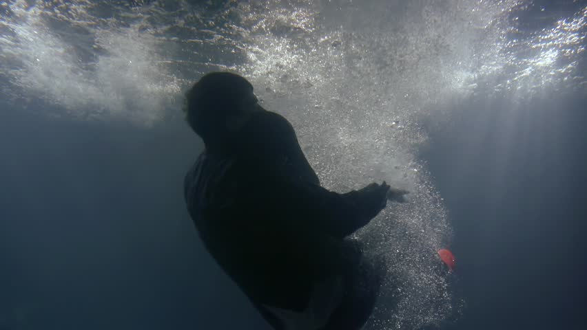 A man in clothes falls back into the water. underwater shooting of a drowning man